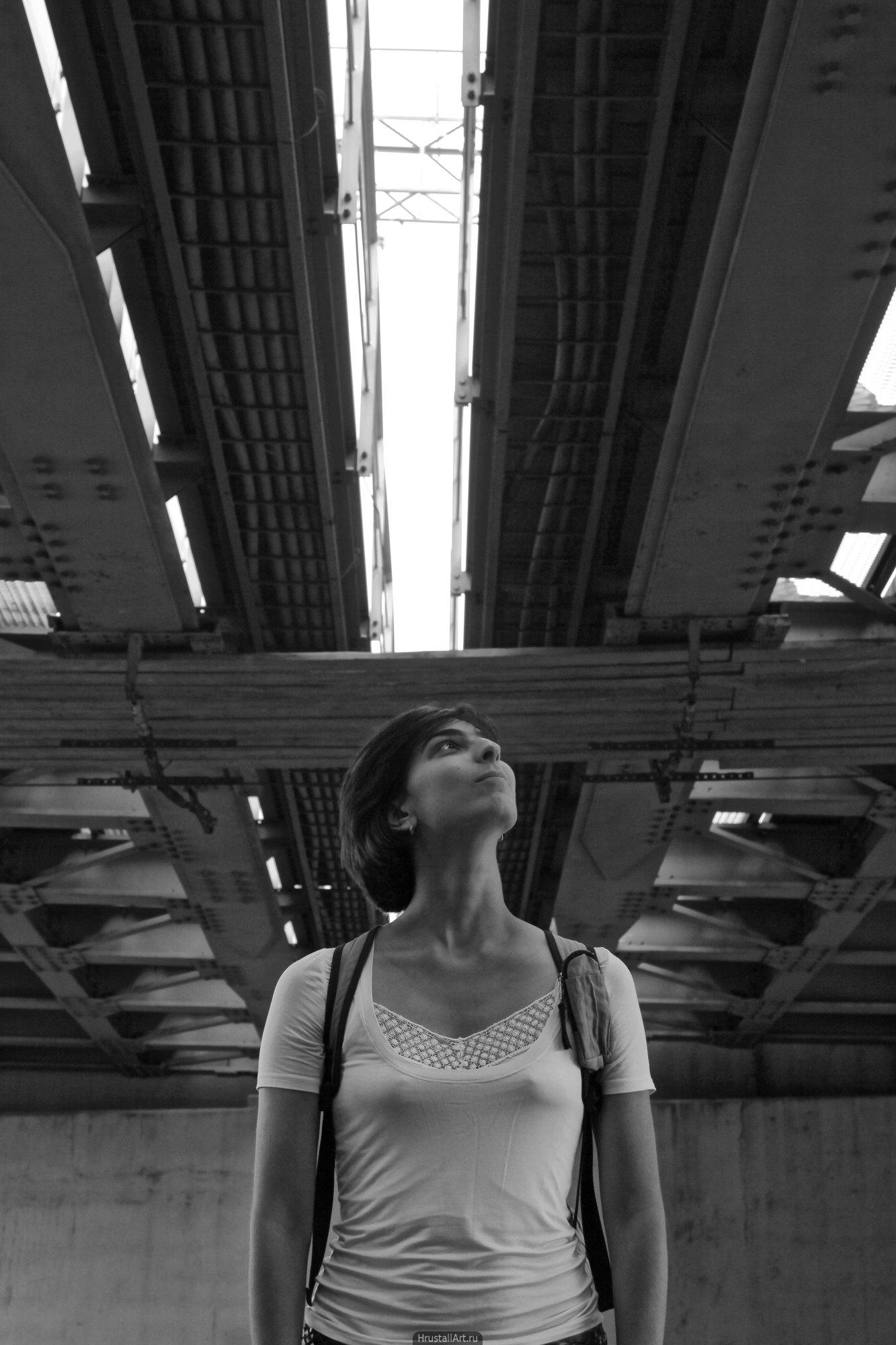 Девушка стоит под полотном железнодорожного моста.
