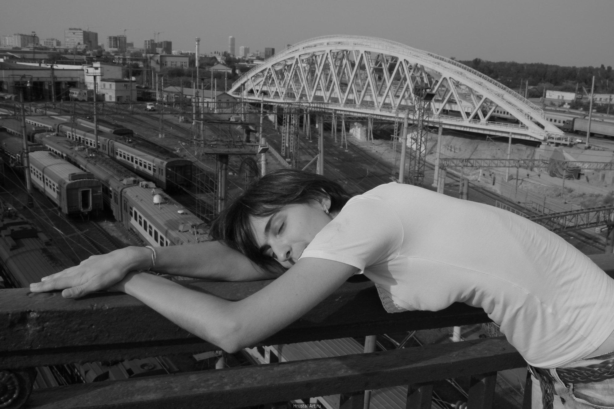 Арки железнодорожного проезда напоминают белые крылья над склонившейся девушкой.